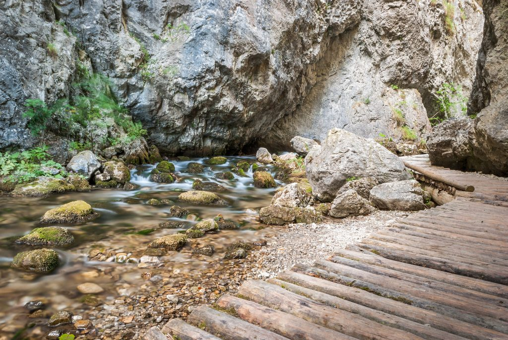This image has an empty alt attribute; its file name is bigstock-Creek-Under-Rocks-With-Wooden-55584386-1024x685.jpg